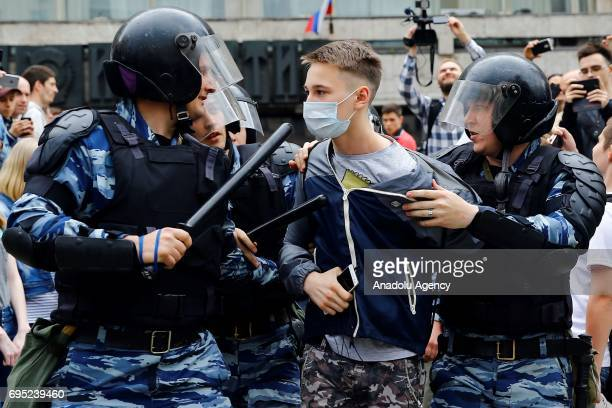Russian police officers take into custody a protester during an unauthorized rally after Russian liberal opposition leader Alexei Navalny called to...