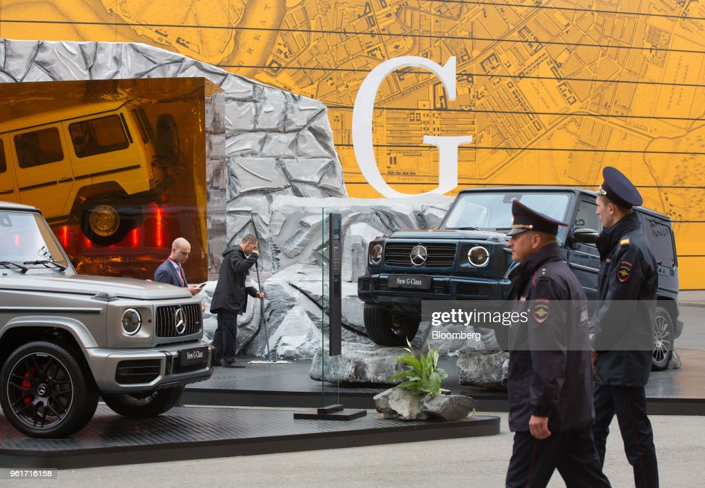 Russian police pass a display of G-Class automobiles on the
