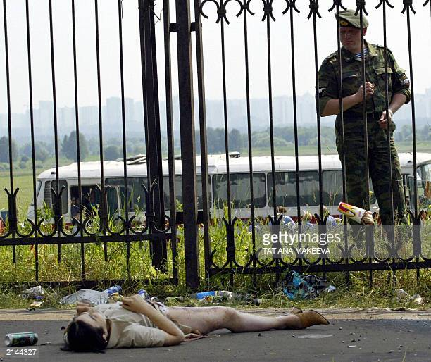 A Russian policeman looks at the dead body of the suspected terrorist near the Tushino airfield 05 July 2003 At least 20 people were killed and 30...