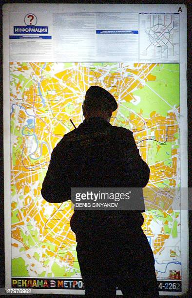 A Russian policeman stands near the site of the explosion as he looks at a Moscow 's map near Rizhskaya subway station in Moscow 31 August 2004 At...
