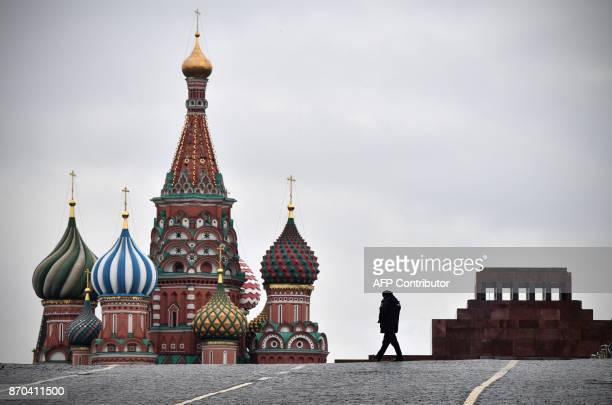 Russian policeman walks in Red Square in Moscow on November 5 with Lenin's mausoleum and St. Basil's Cathedral in the background / AFP PHOTO / Mladen...