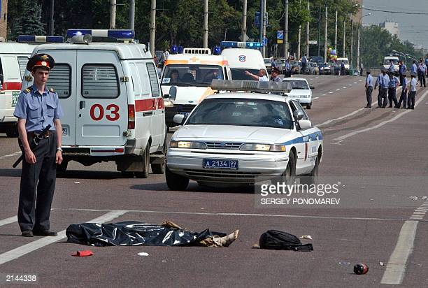 A Russian policemen guards one of the bodies at the site of the blast near Tushino airfield in Moscow 05 July 2003 At least 20 people were killed and...