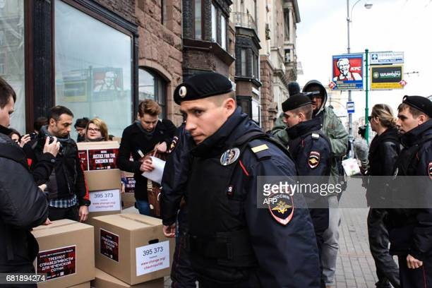 Russian policemen surround Russian gayrights activists standing next to boxes alledgedly containing signed petitions calling for a probe into a...