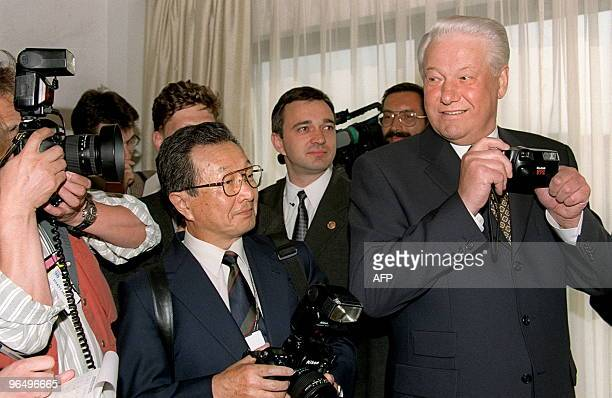 Russian President Boris Yeltsin plays around with a camera with Japanese photographers while waiting for Japanese Prime Minister Ryutaro Hashimoto 15...
