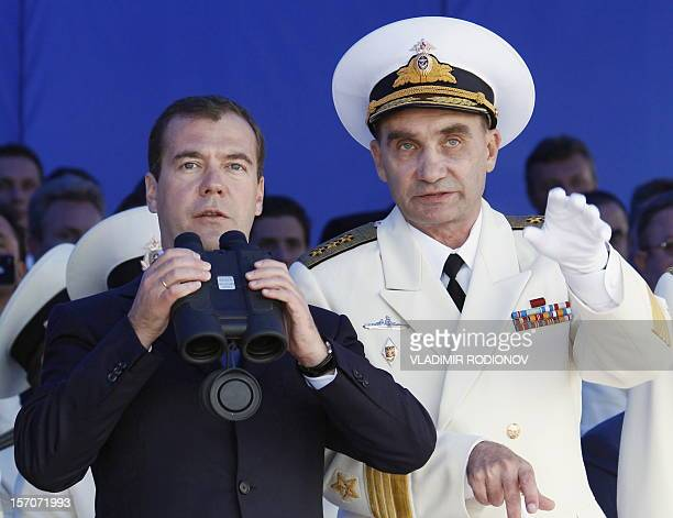 Russian President Dmitry Medvedev and the Commanderinchief of the Navy Vladimir Vysotsky use binoculars to watch a parade duriong a visit at Russia's...