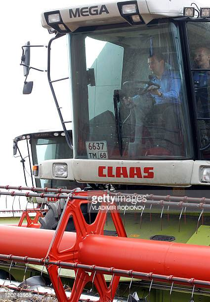 Russian President Dmitry Medvedev drives a combine harvester at a field outside the town of Tambov on July 25 during his visit to the region. AFP...