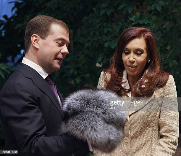 Russian President Dmitry Medvedev gives a traditional Russian fur hat to Argentine President Cristina Kirchner at the Kremlin in Moscow on December...