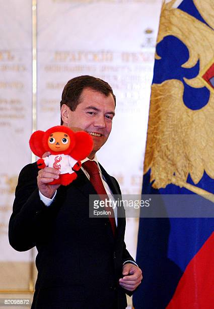 Russian President Dmitry Medvedev holds a mascot presented to him by Russian Olympic basketball team player Andrei Kirilenko during a wellwishing...
