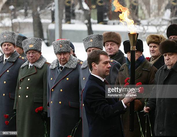 Russian President Dmitry Medvedev holds the torch as he takes part in the lighting up of the eternal flame, at the Tomb of the Unknown Soldier, on...