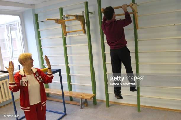 Russian President Dmitry Medvedev pulls himself up as he visits a gymnasium in a primary school outside of Sochi on December 2010 in the Black Sea...