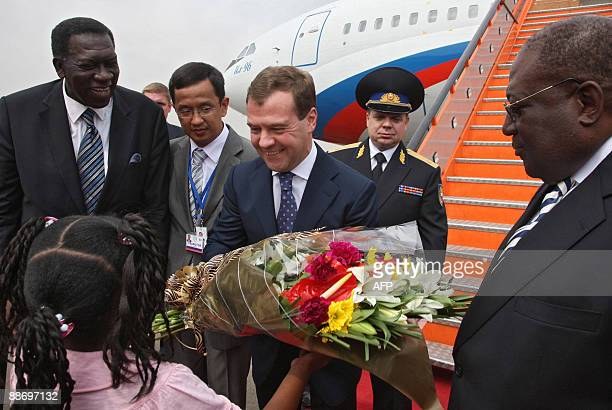 Russian President Dmitry Medvedev receives flowers from a girl while being greeted by Angolan Prime Minister Antonio Paulo Kassoma and Foreign...