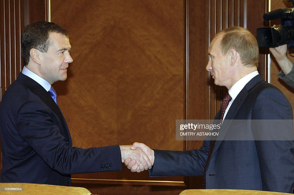 Russian President Dmitry Medvedev (L) shakes hands with Prime Minister Vladimir Putin (R) outside Moscow in Gorki on May 24, 2010. The ruling United Russia party of Russia's strongman Prime Minister Vladimir Putin was scrambling to explain how it suffered a rare defeat to the Communists in a local election in Siberia.