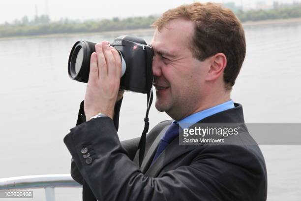 Russian President Dmitry Medvedev takes pictures with his Leica camera as he has a motor ship tour on Amur river July 3 2010 in the city of...
