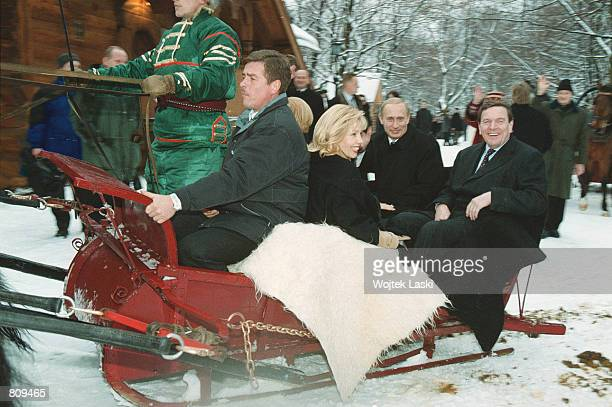 Russian President Vladimir Putin 2nd right rides in a troika the traditional Russian sled pulled by three horses with German Chancellor Gerhard...