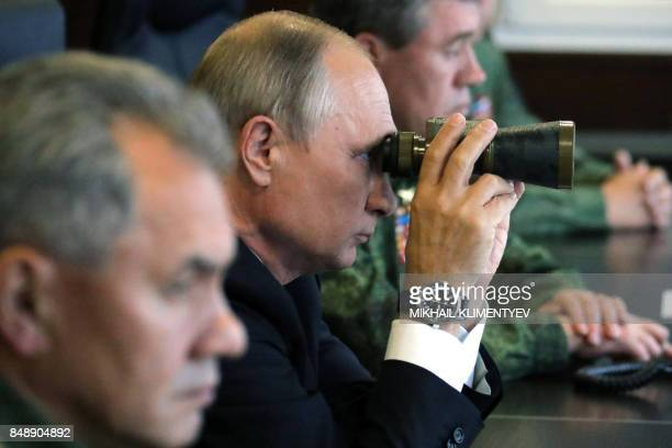 Russian President Vladimir Putin , accompanied by Defence Minister Sergei Shoigu , uses a pair of binoculars as he inspects the joint Zapad-2017...