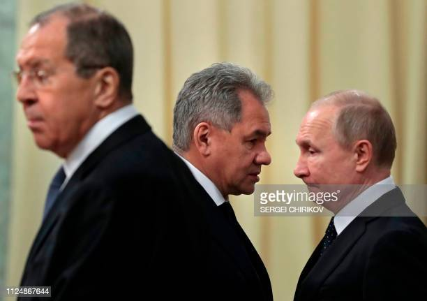 Russian President Vladimir Putin , accompanied by Defence Minister Sergei Shoigu and Foreign Minister Sergei Lavrov, waits for a meeting with his...