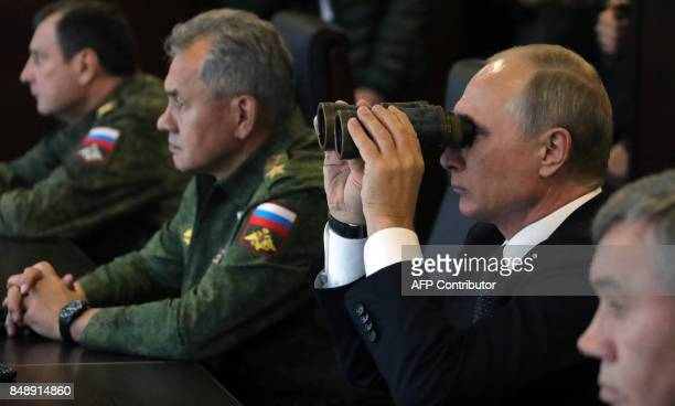Russian President Vladimir Putin accompanied by Defence Minister Sergei Shoigu watches the joint Zapad2017 Russian military exercises with Belarus at...