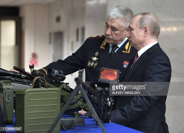 Russian President Vladimir Putin accompanied by Interior Minister Vladimir Kolokoltsev examines weapons as he tours an exhibition before the annual...