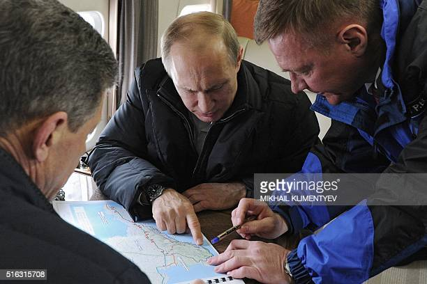 Russian President Vladimir Putin accompanied with Deputy Prime Minister Dmitry Kozak and head of the Federal Road Agency Roman Starovoit points at...