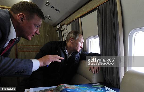 Russian President Vladimir Putin accompanied with head of the Federal Road Agency Roman Starovoit inspects the site of the underconstruction bridge...
