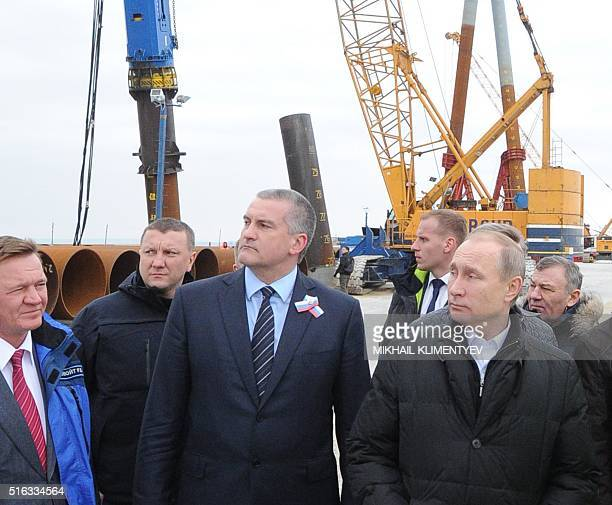 Russian President Vladimir Putin accompanied with Russian head of Crimea Sergei Aksyonov and head of the Federal Road Agency Roman Starovoit inspects...