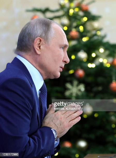 Russian President Vladimir Putin addresses his annual press conference via a video link at the Novo-Ogaryovo state residence outside Moscow on...