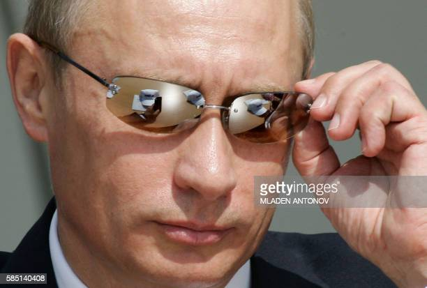 Russian President Vladimir Putin adjusts his sunglasses during the MAKS-2005 International air and space show in Zhukovsky, some 50 kms from Moscow,...