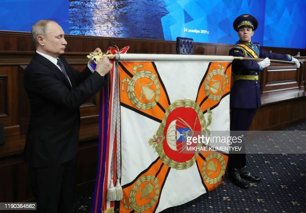 Russian President Vladimir Putin adjusts the ribbon of Kutuzov's order on the Standart of Russia's 104th airborne assault regiment after attending...