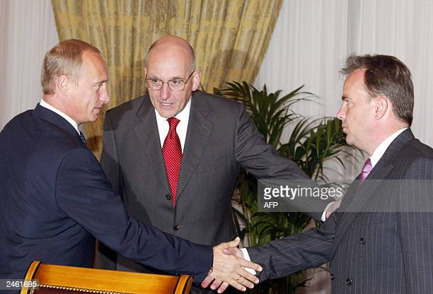 Russian President Vladimir Putin and AngloDutch oil company Royal Dutch/Shell President in Russia John Barry shake hands as Shell's Chairman Philip...