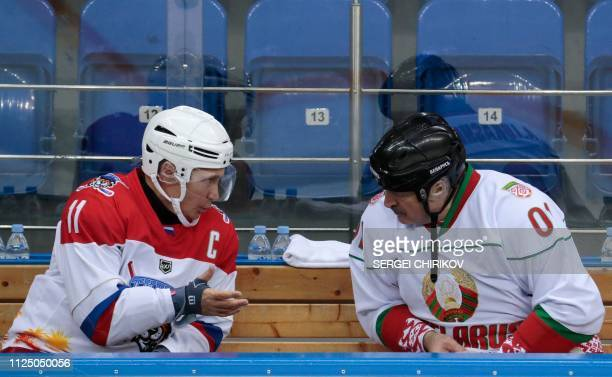 Russian President Vladimir Putin and Belarus President Alexander Lukashenko speak as they take part in an ice hockey match at Shayba Arena in the...