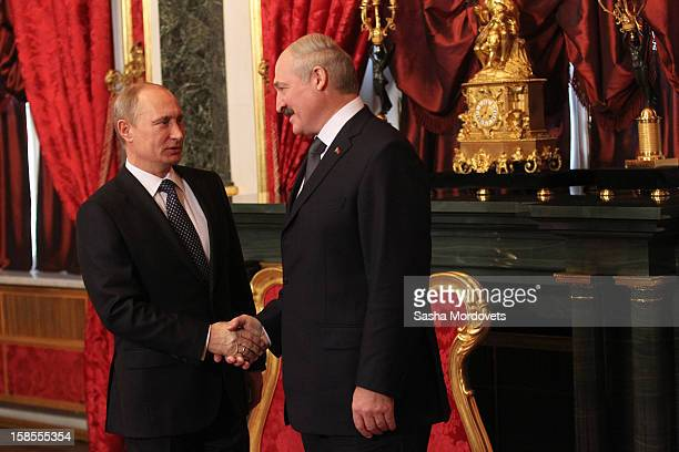 Russian President Vladimir Putin and Belarus President Alexander Lukashenko shake hands as they attend the Summit of the Collective Security Treaty...