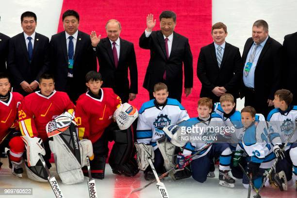 Russian President Vladimir Putin and Chinese President Xi Jinping wave as they pose for photos with the Chinese and Russian youth Ice Hockey teams...