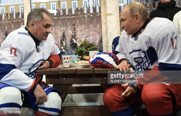 Russian President Vladimir Putin and Defence Minister Sergei Shoigu take part in the Night Hockey League match on the GUM department store skating...