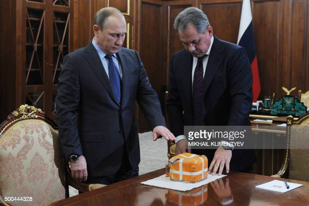 TOPSHOT Russian President Vladimir Putin and Defence Minister Sergei Shoigu examine at the NovoOgaryovo residence outside Moscow on December 8 the...