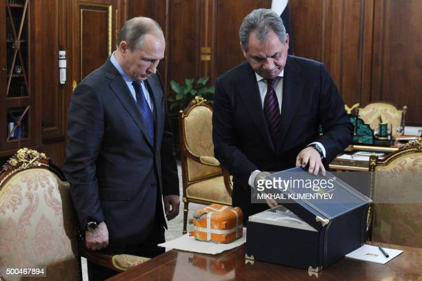 Russian President Vladimir Putin and Defence Minister Sergei Shoigu examine at the NovoOgaryovo residence outside Moscow on December 8 the flight...