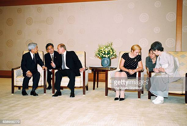 Russian President Vladimir Putin and Emperor Akihito talk while Empress Michiko and Putin's wife Lyudmila talk during their meeting at the Imperial...