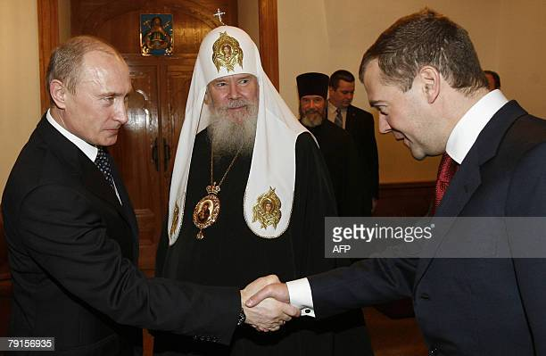 Russian President Vladimir Putin and First Deputy Prime Minister Dmitry Medvedev Russia's top presidential candidate shake hands as Russian Orthodox...