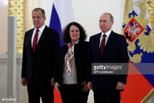 Russian President Vladimir Putin and France's ambassador to Russia Sylvie Bermann pose for a photo with Foreign Minister Sergei Lavrov seen behind...