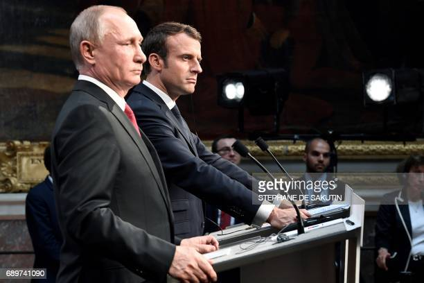 Russian President Vladimir Putin and French President Emmanuel Macron look on during a joint press conference in the Galerie des Batailles following...