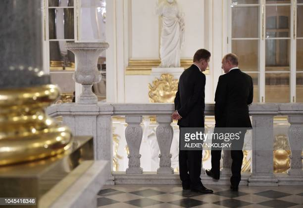 Russian President Vladimir Putin and Gazprom's chief executive Alexei Miller talk at the State Hermitage Museum in Saint Petersburg on October 3 2018