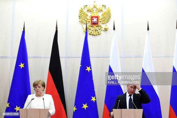 Russian President Vladimir Putin and German Chancellor Angela Merkel attend a press conference during their meeting in Sochi on May 18 2018