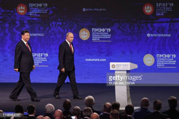 Russian President Vladimir Putin and his Chinese counterpart Xi Jinping arrive for a plenary session of the St. Petersburg International Economic...