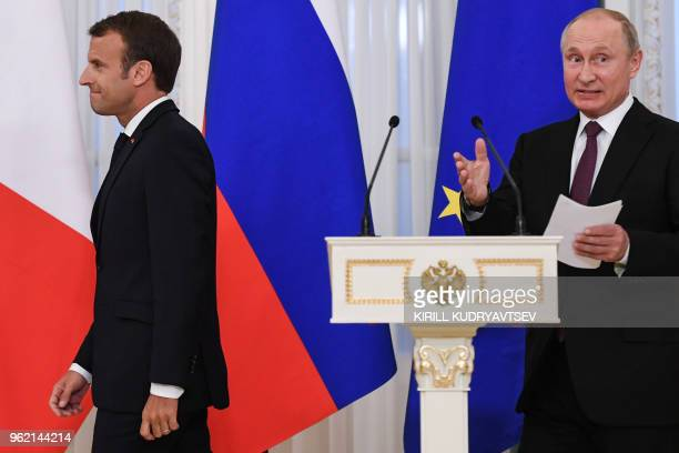 Russian President Vladimir Putin and his French counterpart Emmanuel Macron arrive to attend a signing ceremony following their talks at the...