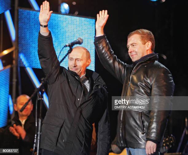 Russian President Vladimir Putin and his likely successor Dmitry Medvedev wave as they make a surprise appearance at a rock concert near Red Square...