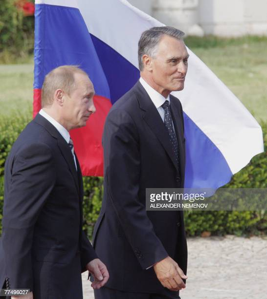 Russian President Vladimir Putin and his Portugese counterpart Cavaco Silva pass a Russian national flag during a welcoming ceremony in Lisbon 25...