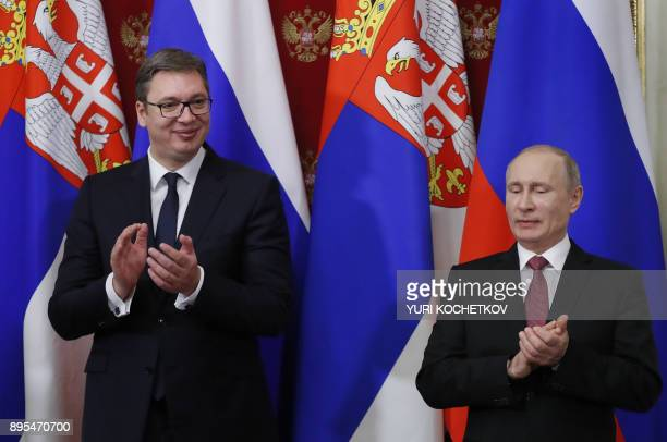 Russian President Vladimir Putin and his Serbian counterpart Aleksandar Vucic applaud during a signing ceremony following their meeting at the...
