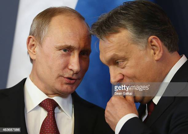 Russian President Vladimir Putin and Hungarian Prime Minister Viktor Orban converse during a signing ceremony of several agreements between the two...