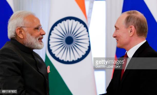 Russian President Vladimir Putin and Indian Prime Minister Narendra Modi shake hands after a signing ceremony following their meeting on the...