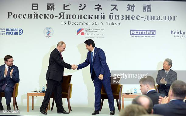 Russian President Vladimir Putin and Japanese Prime Minister Shinzo Abe shake hands at a JapanRussia business dialogue meeting at Keidanren Kaikan on...