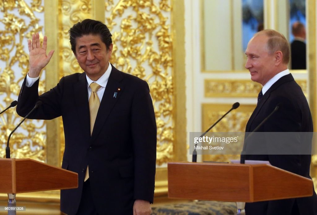 Russian President Vladimir Putin (R) and Japanese Prime Minister Shinzo Abe (L) wave during a video communication session with crew of International Space Station at the Kremlin on May 26, 2018 Moscow, Russia. Shinzo Abe is having a state visit to Russia.